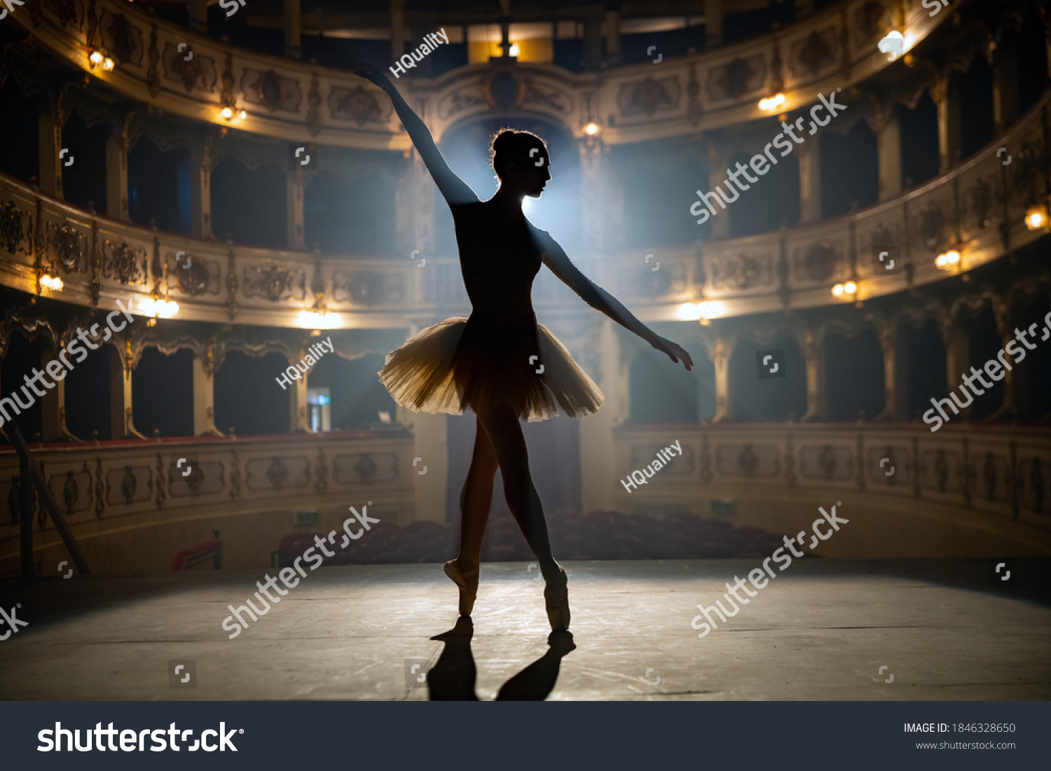 Silhouette of a young graceful classical ballet female dancer in white tutu is performing a choreography on classic theatre stage with dramatic lighting before start of a show. #1846328650