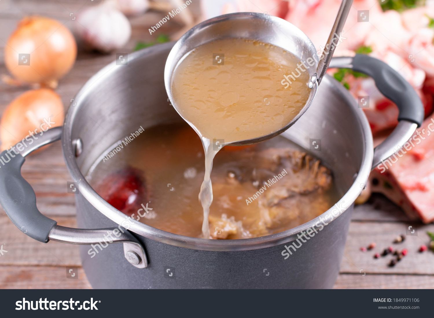 Saucepan with bouillon with a ladle on the table. Bone broth #1849971106