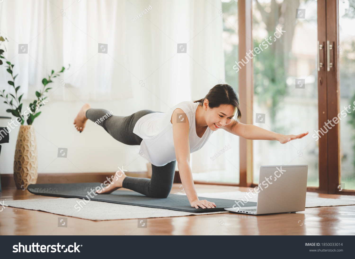 Smiling Asian woman doing one arm one leg plank to exercise core muscle online workout class from laptop at home in living room. Self isolation and workout at home during COVID-19. #1850033014