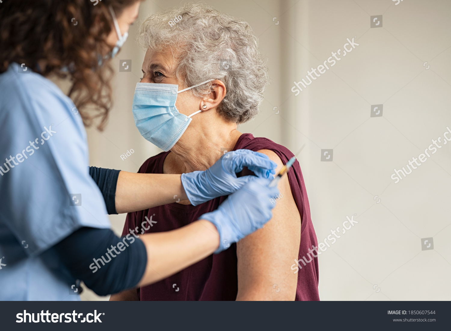 General practitioner vaccinating old patient in clinic with copy space. Doctor giving injection to senior woman at hospital. Nurse holding syringe before make Covid-19 or coronavirus vaccine. #1850607544