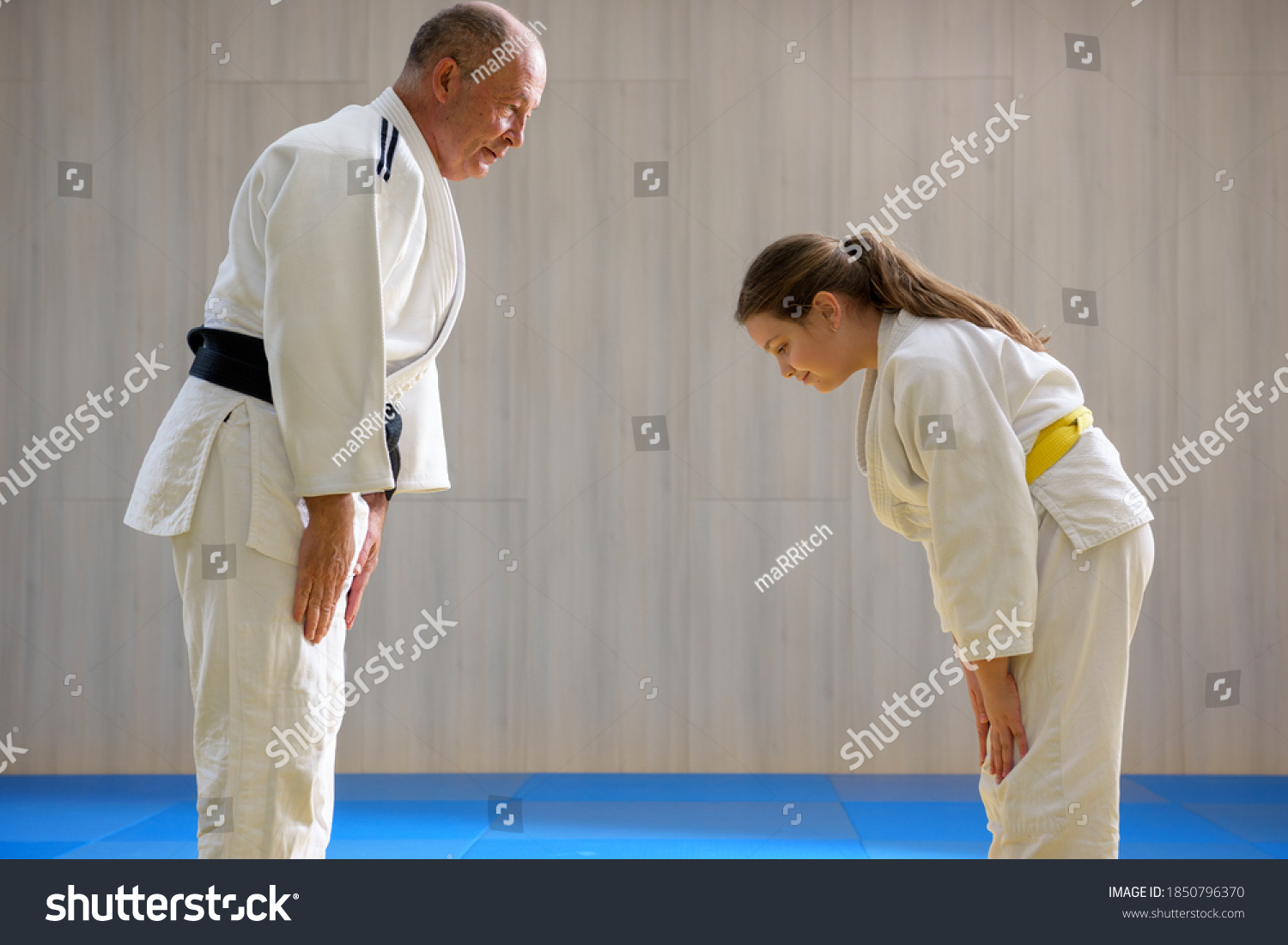 Young female judo girl showing respect to old judo teacher #1850796370