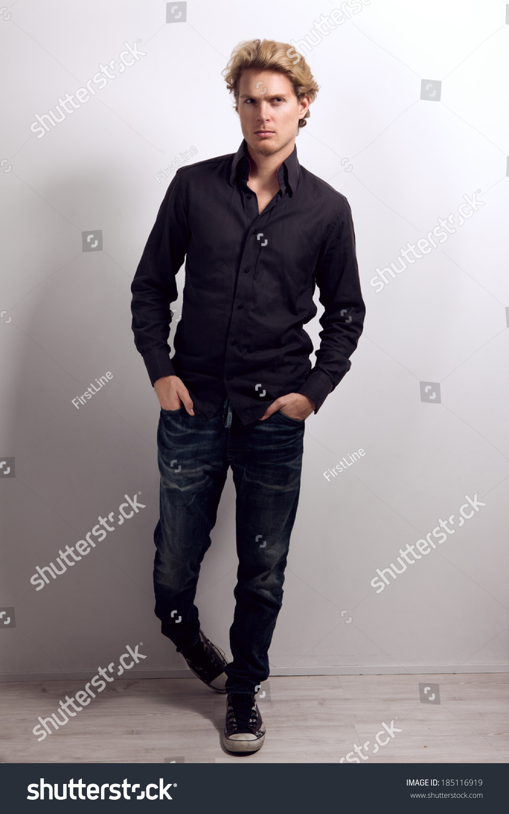 Attractive male with blonde hair dressed in black shirt Black shirt blue jeans