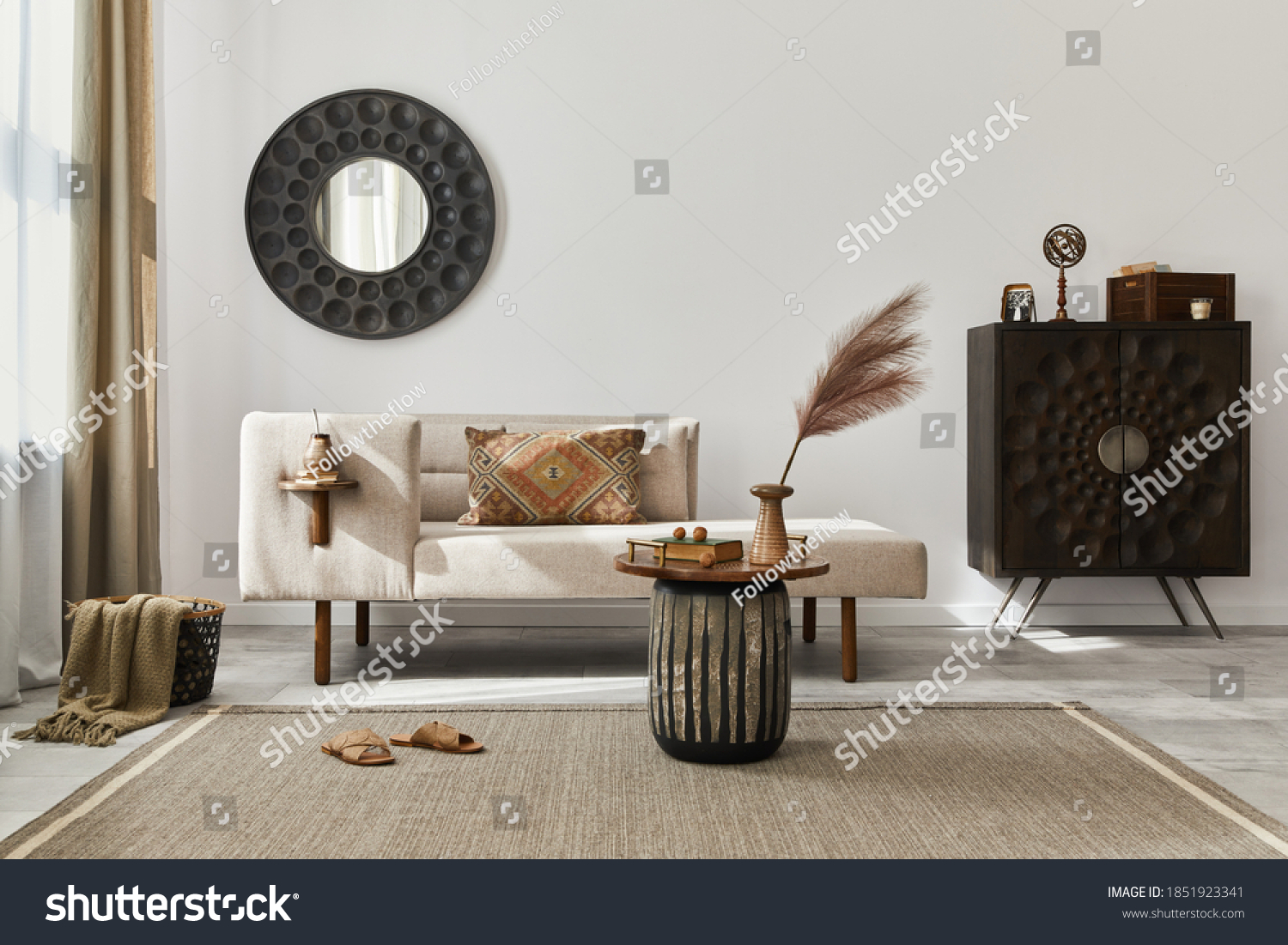 Interior design of ethnic living room with modern commode, round mirror, decoration, furniture and personal accessories. Template. White wall. #1851923341