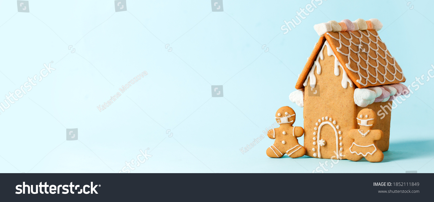 Happy New Year's set of house, gingerbread man in face mask from ginger biscuits glazed sugar icing decoration on blue background, minimal seasonal pandemic winter holiday banner, stay home #1852111849