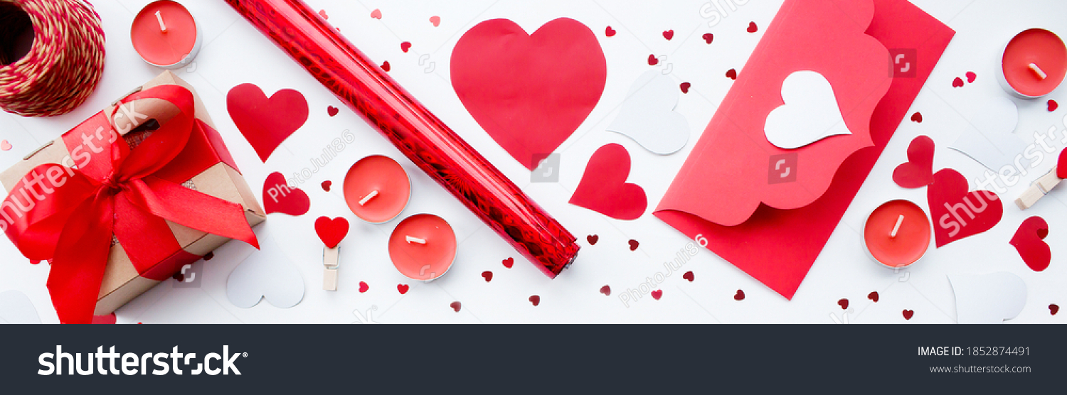 Banner. Valentine's Day. Flat lay of red hearts, handmade gift boxes, red roses and a notebook for writing on a white background. Copy space. The concept of holidays and love. #1852874491