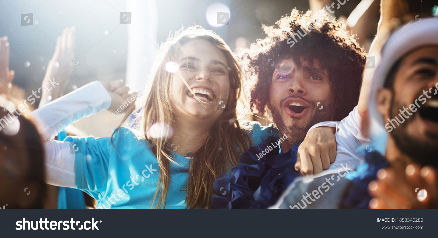 Cheerful couple cheering at a live soccer match. Group of people in the stadium cheering argentina football team. #1853340280