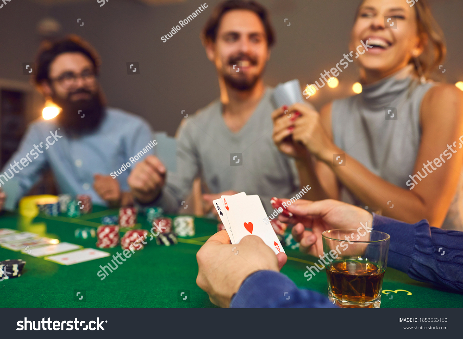 Mans hands holding playing cards with aces, poker chips and drink in glass during poker gambling over smiling friends faces at background, close-up, selective focus. Gambling, casino, poker concept #1853553160