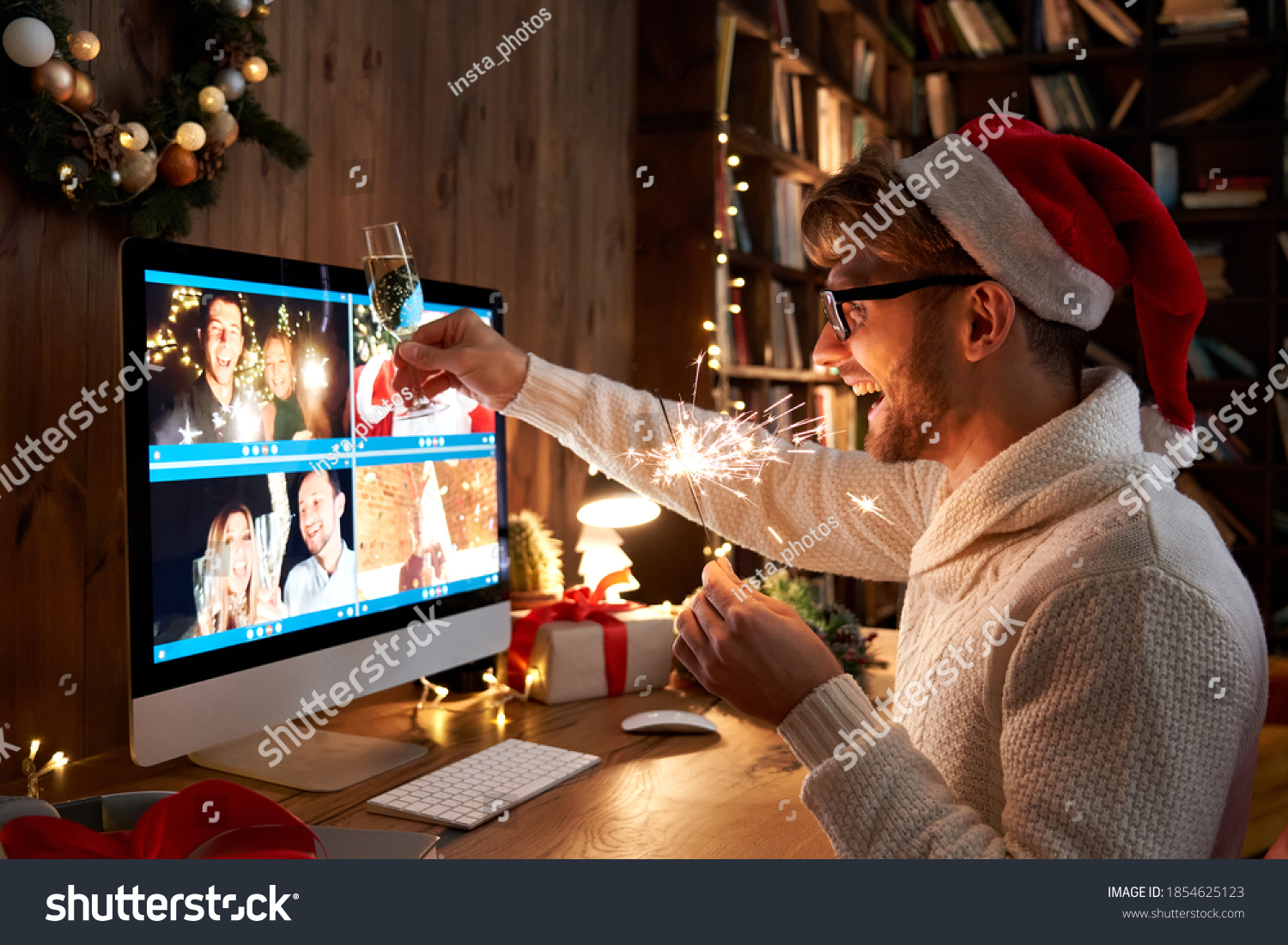 Young man wearing Christmas hat drinking champagne holding sparkler talking to friends on virtual zoom video call celebrate Happy New Year party in distance online conference chat on computer at home. #1854625123