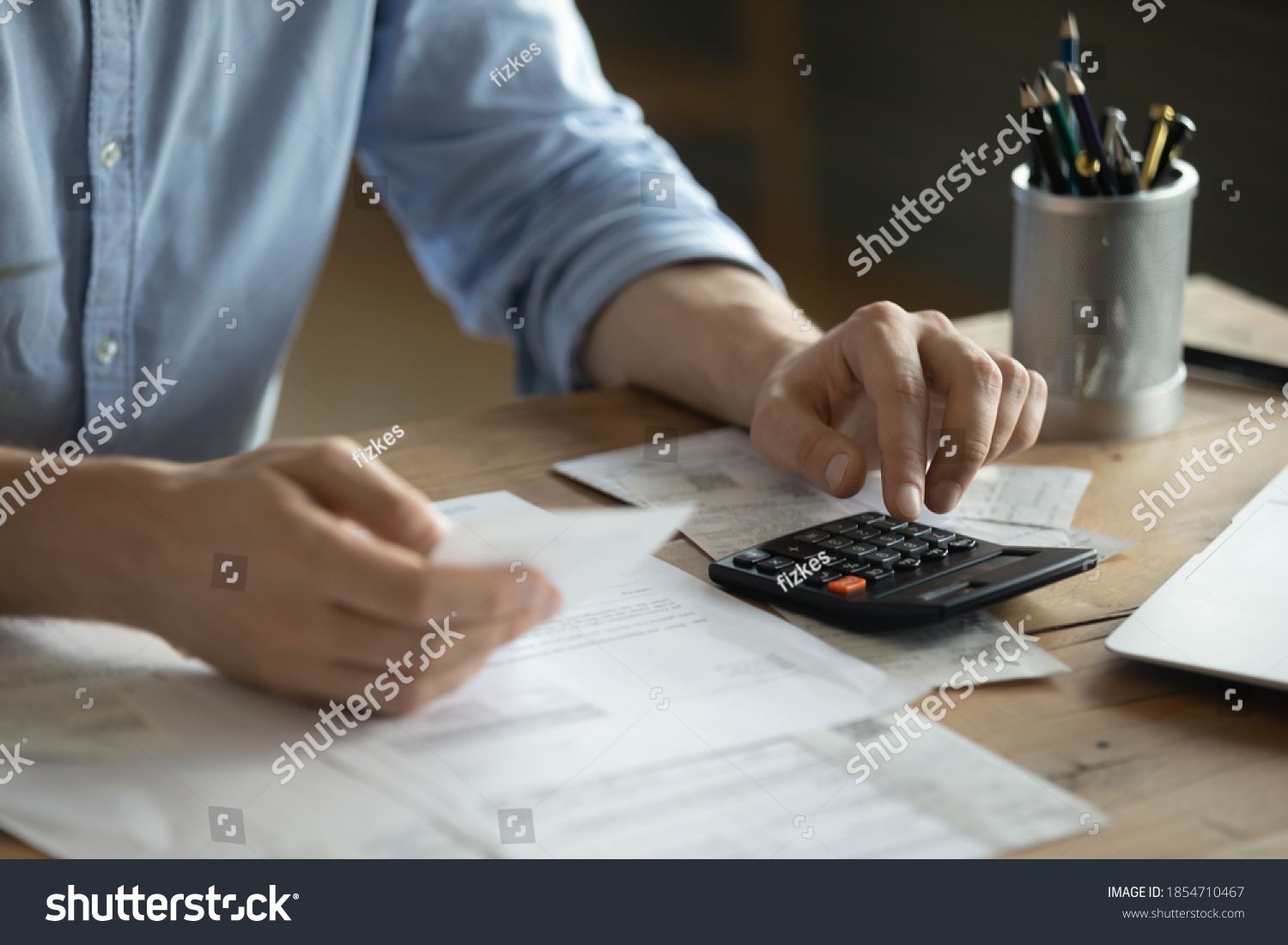 Personal finance management, accounting concept. Close up view man sitting at table using calculator performs arithmetic operations calculates costs per month, manage family budget, control expenses #1854710467