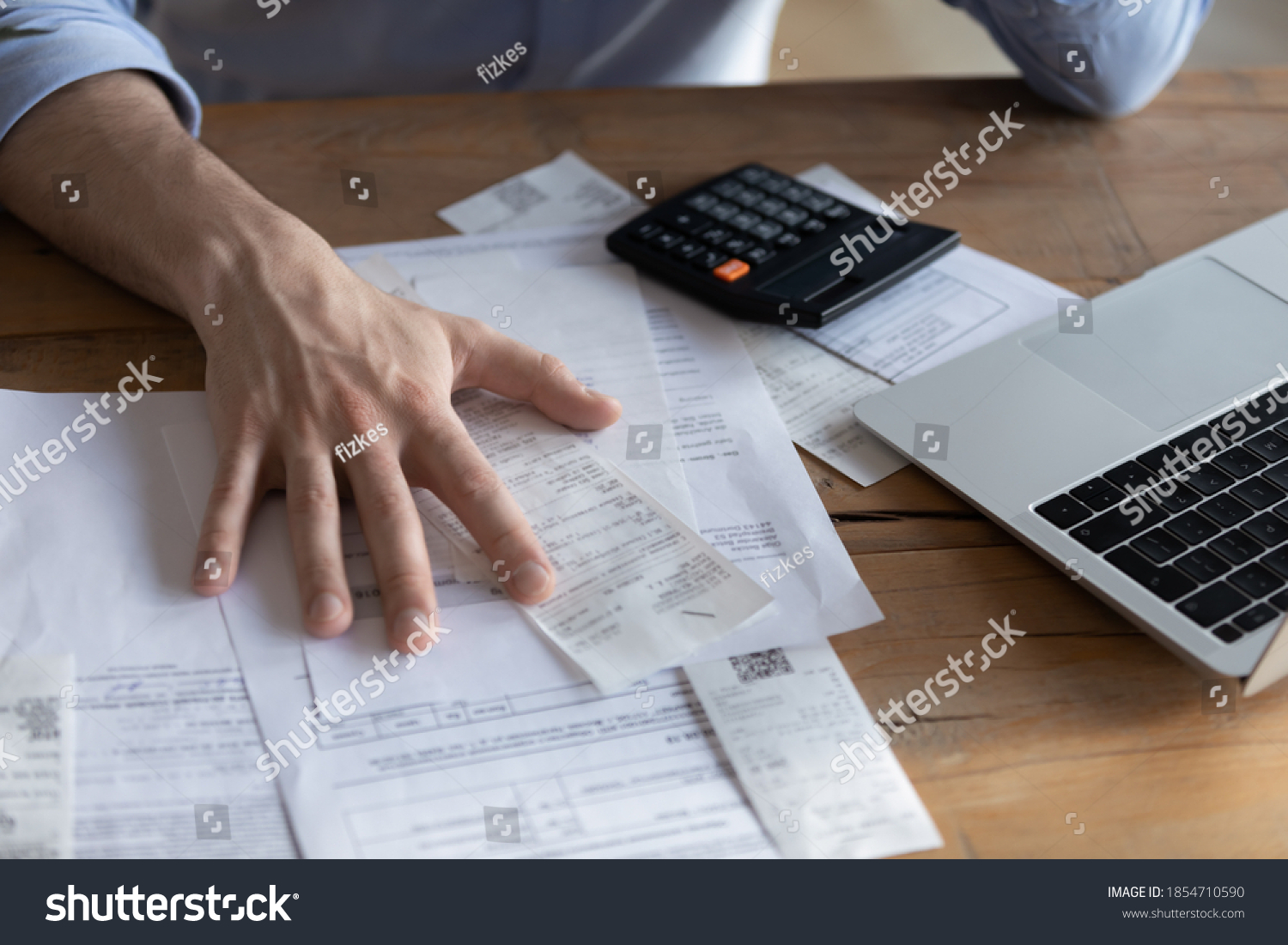 Individual entrepreneur make analysis of firm expenses, accountant do paperwork concept. On desk lot of receipts, calculator and laptop close up view. Man sit at table reviewing bills, managing budget #1854710590