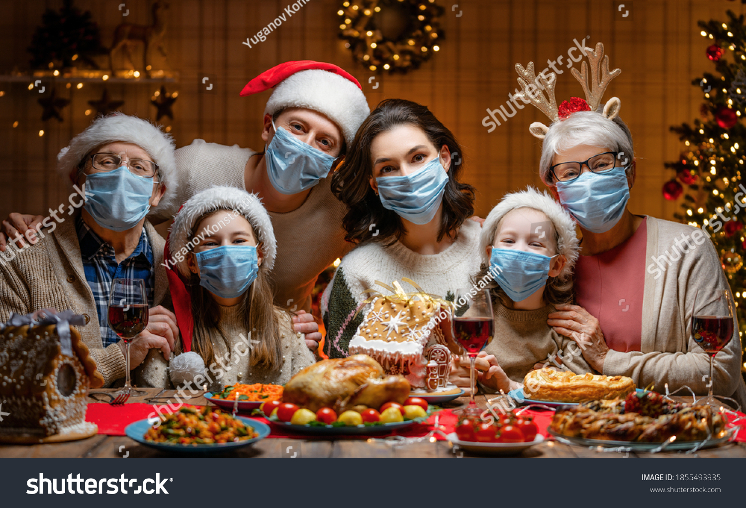 Merry Christmas! Happy family are having dinner at home. Celebration holiday and togetherness near tree. People are wearing facemasks. #1855493935