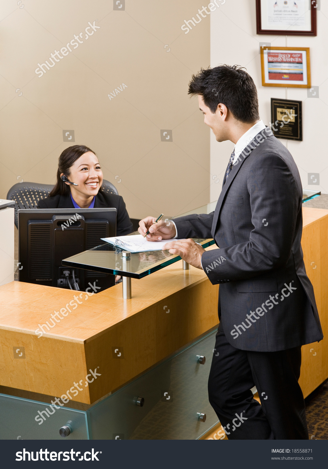 friendly receptionist greeting man at front desk stock photo friendly receptionist greeting man at front desk preview save to a lightbox