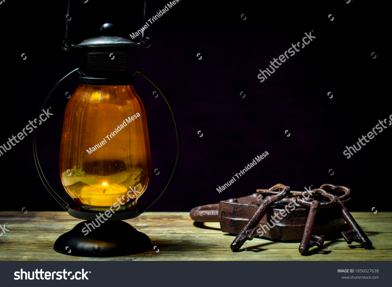 Candle lamp next to a padlock and keys, on dark background