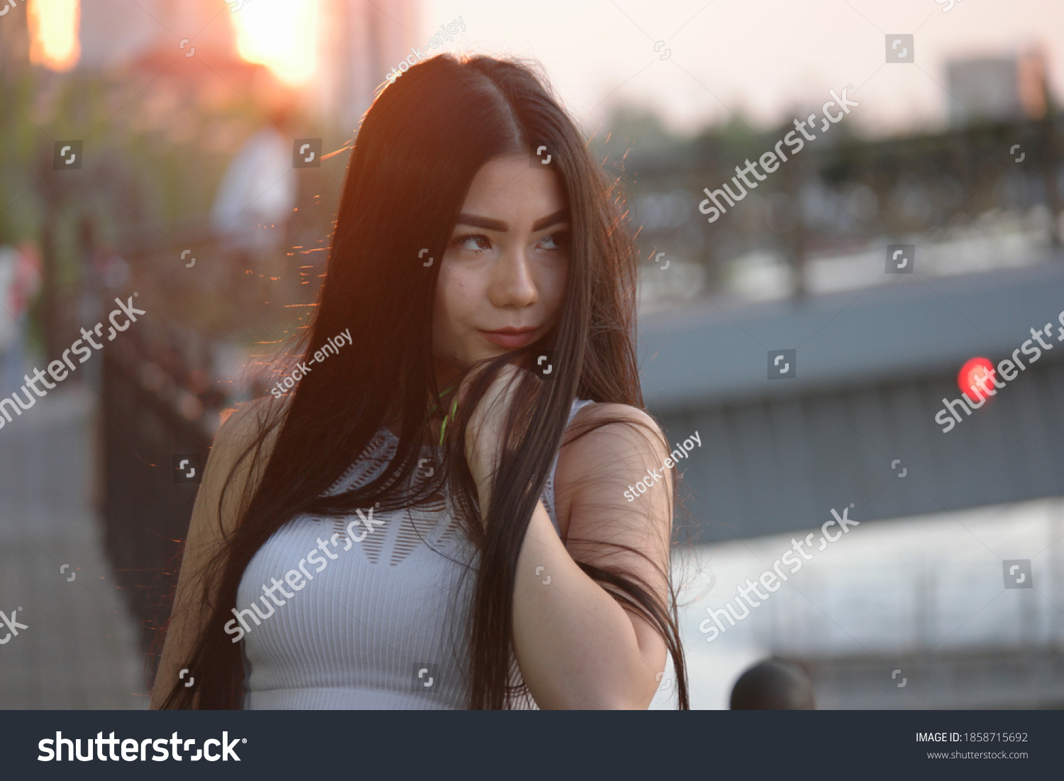 Melancholic asian girl posing in sunset time on embankment looking away and leaning her chin on her hand, copyspace. Lovesick sweetheart in depression.