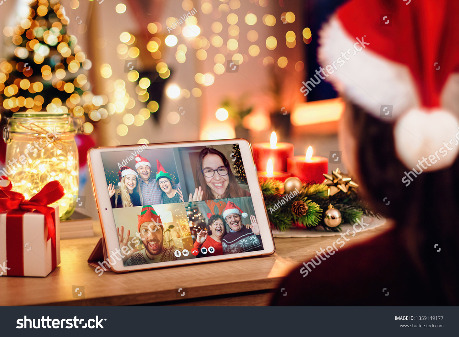 Girl having a Christmas video call with her happy family. Concept of families in quarantine during Christmas because of the coronavirus. Xmas still life with a tablet in a cozy room #1859149177