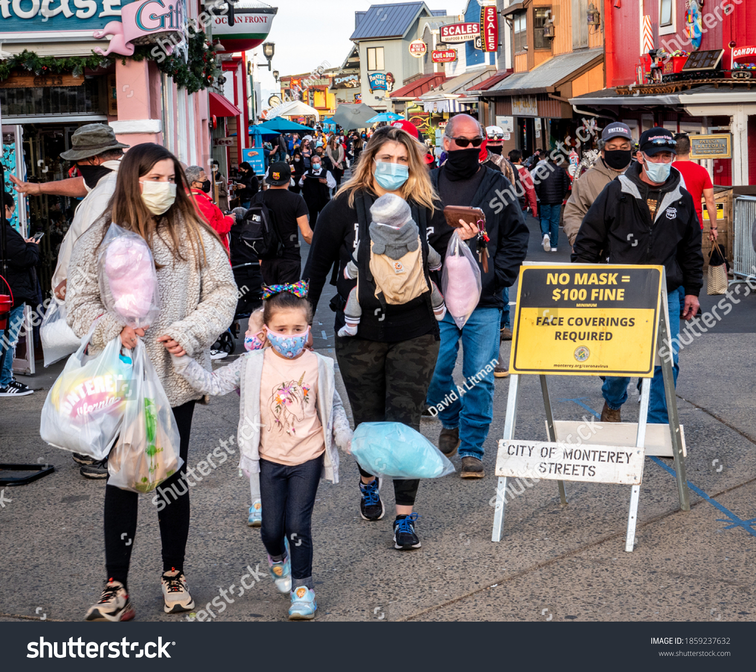 Monterey, California - November 21, 2020: Large crowds of people flock to Fisherman's Wharf, despite the global Covid19 Coronavirus pandemic, but don masks to avoid a $100 fine.