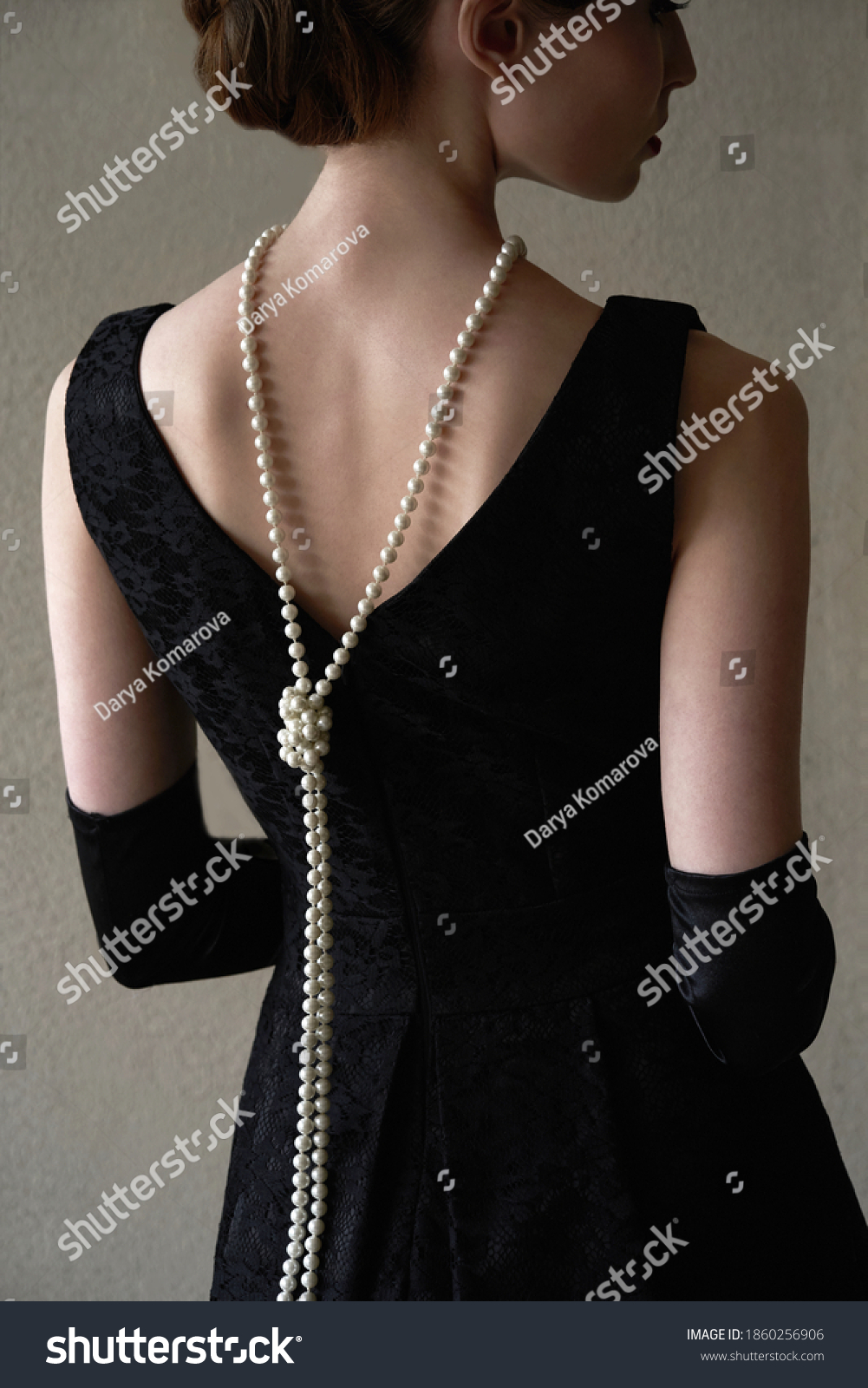 Beautiful woman figure in profile in a black dress and pearls in the style of 20-30 years of the XX century     #1860256906
