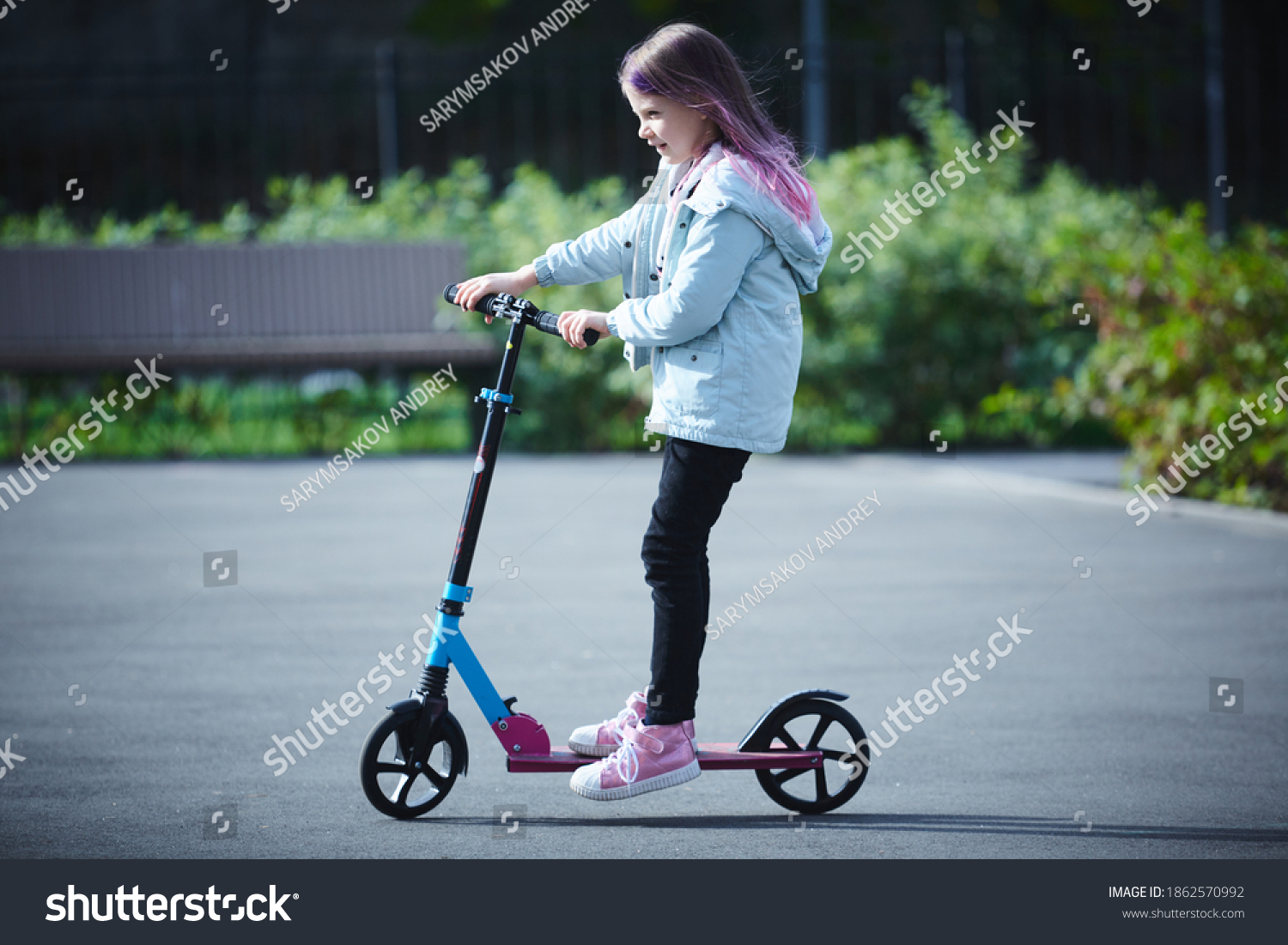 Happy beautiful girl is riding along the street on the kick scooter on a windy day. Baby having free time playing. The concept of a healthy lifestyle. Kids sport #1862570992