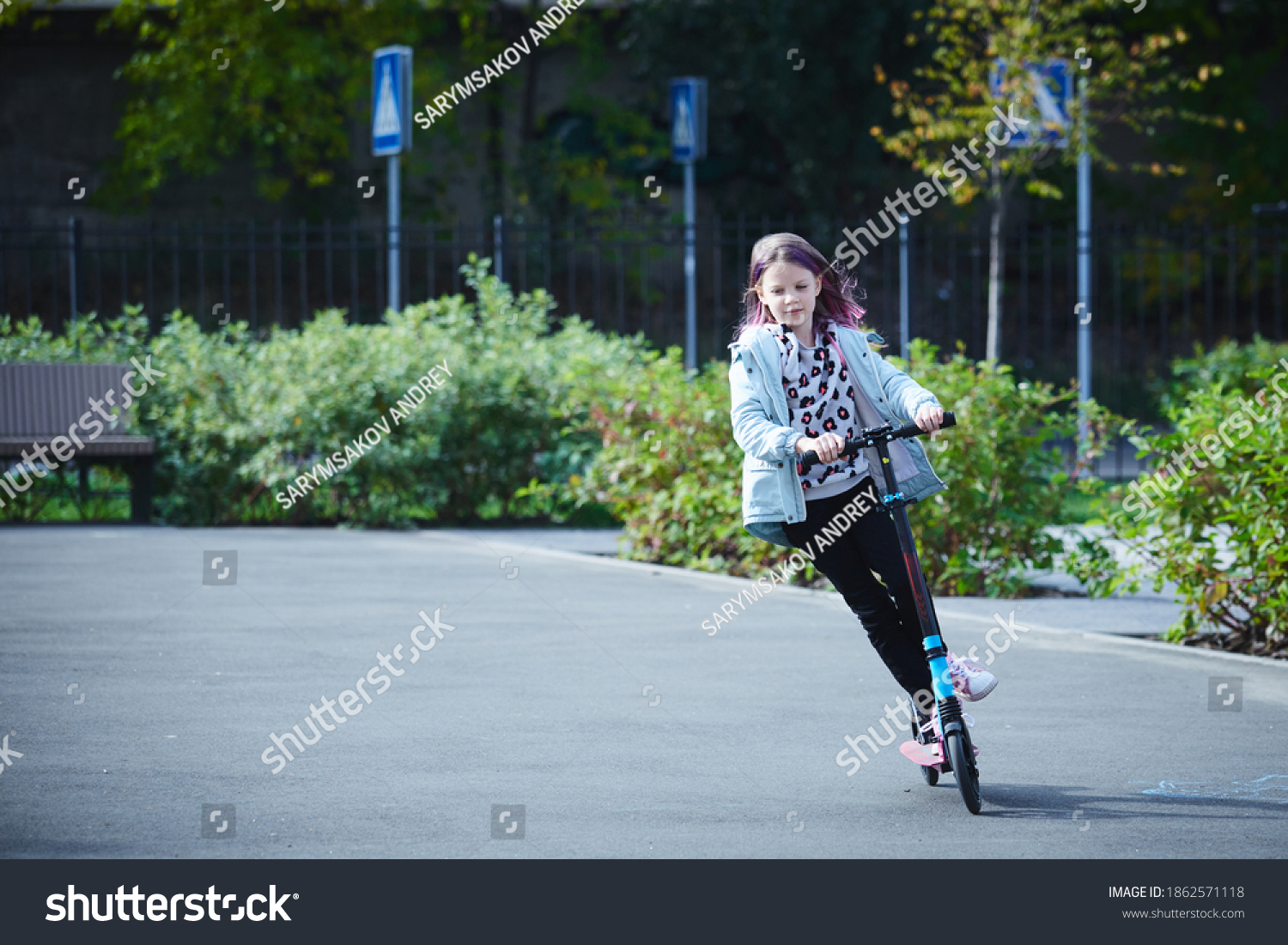Happy beautiful girl is riding along the street on the kick scooter on a windy day. Baby having free time playing. The concept of a healthy lifestyle. Kids sport #1862571118