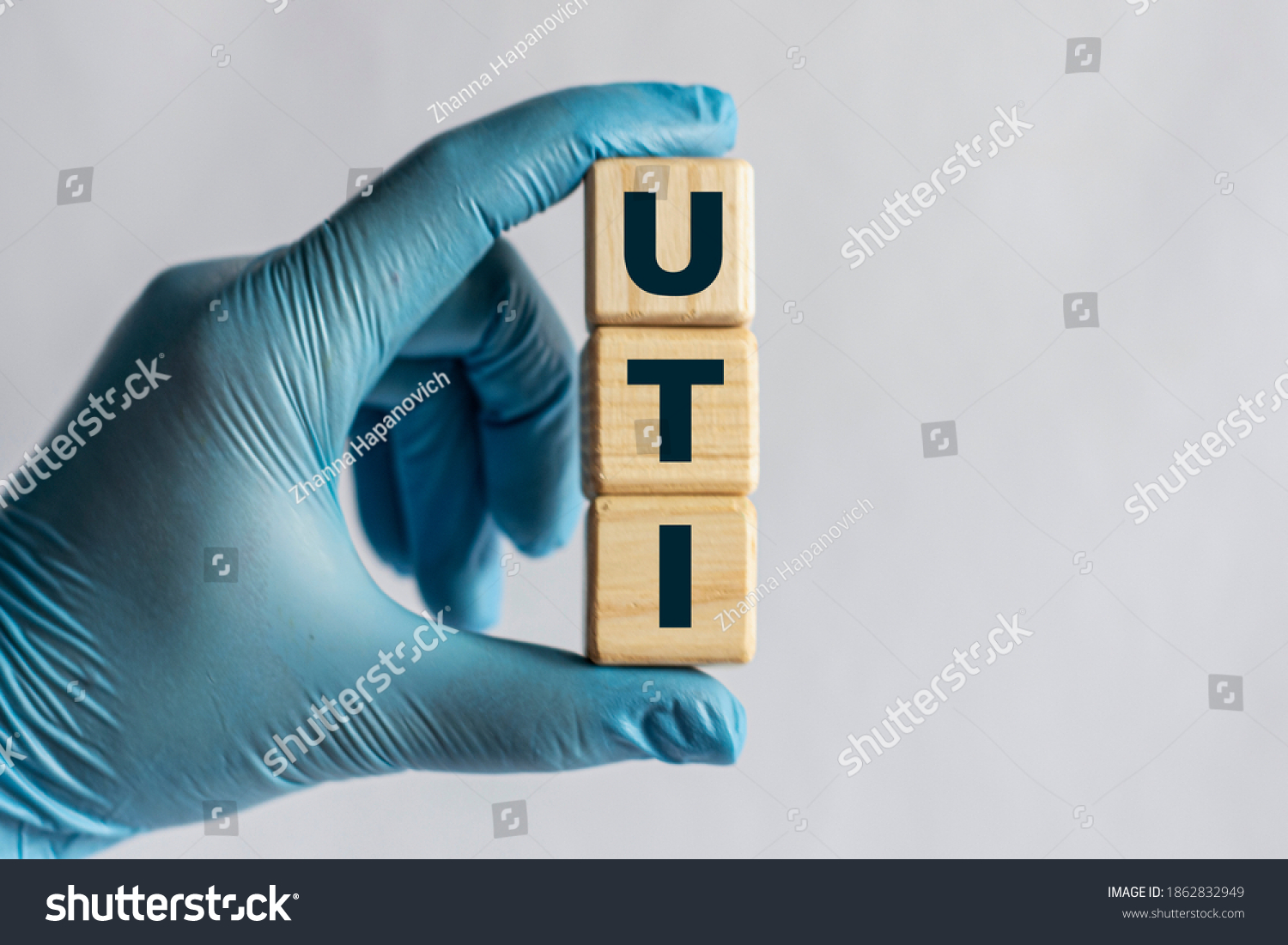 UTI (Urinary Tract Infection) - is an acronym on cubes held by a hand in a blue glove. Medical concept. #1862832949