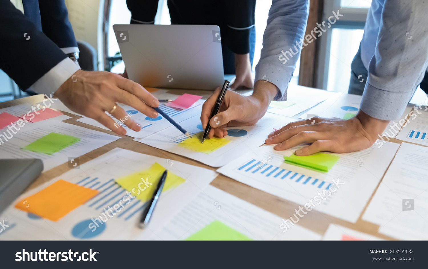 Close up of diverse businesspeople working on project startup presentation in team, comparing statistic data, studying values on graph diagrams, analyzing trends patterns, making notes on paper sheets #1863569632