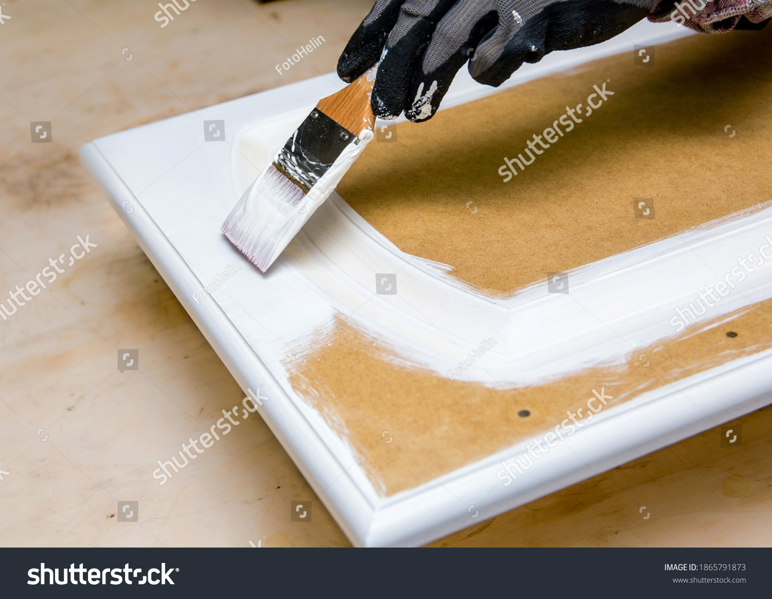 Repainting kitchen cabinet doors with white chalk paint indoors at home. Giving old kitchen new look concept. Hand holding a paint brush tool with paint against old cupboard door. #1865791873