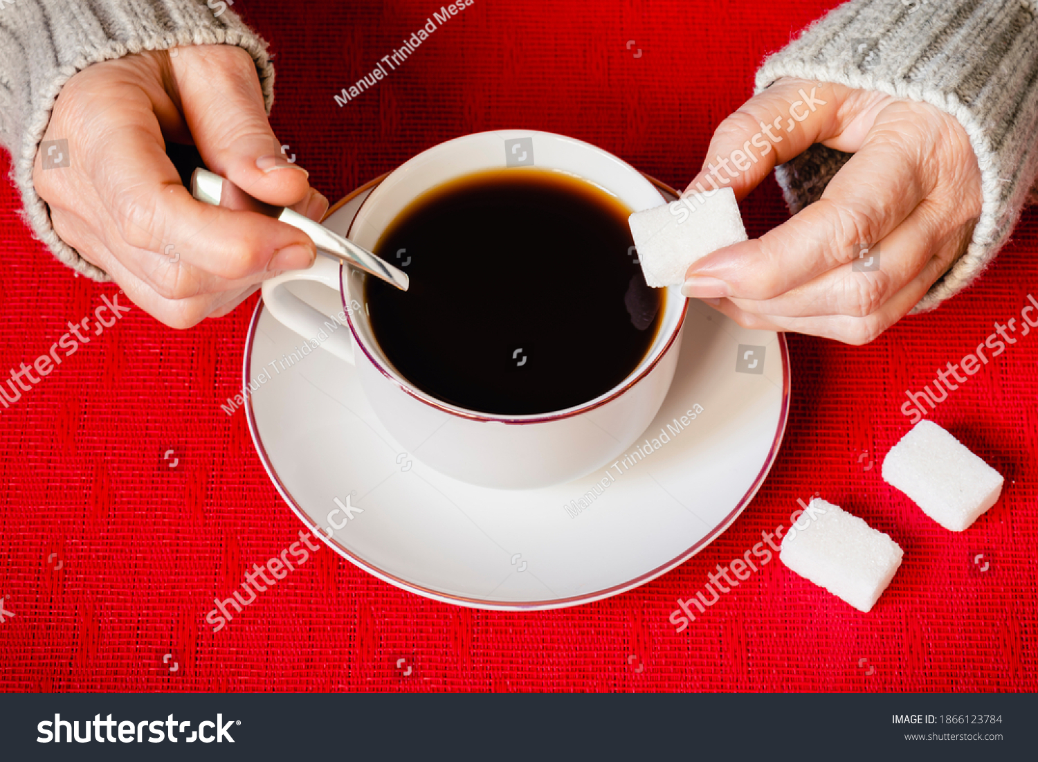 A hand putting a sugar cube in a cup of coffee, on a red tablecloth