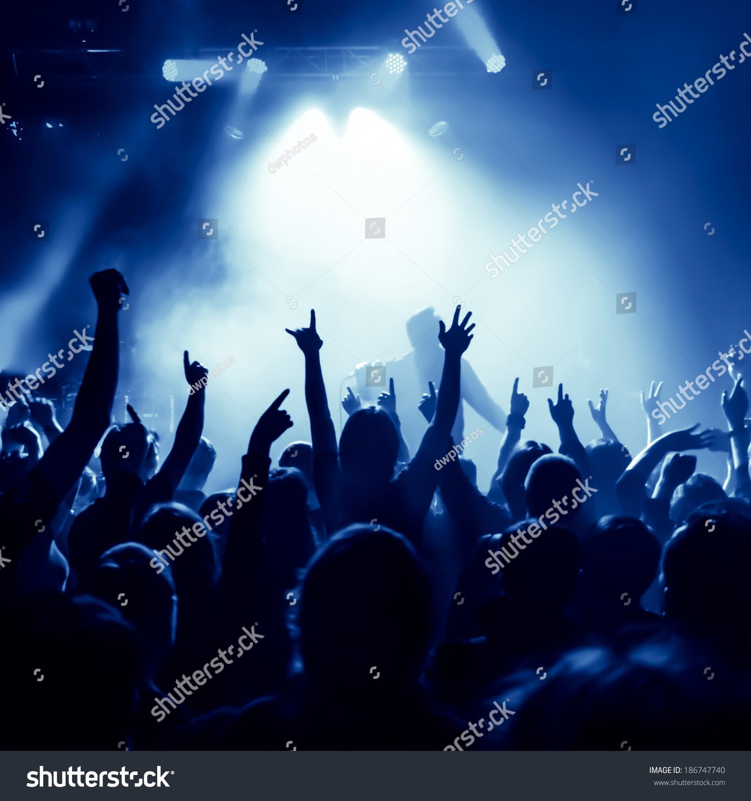 silhouettes of concert crowd in front of bright stage lights, singer on stage #186747740