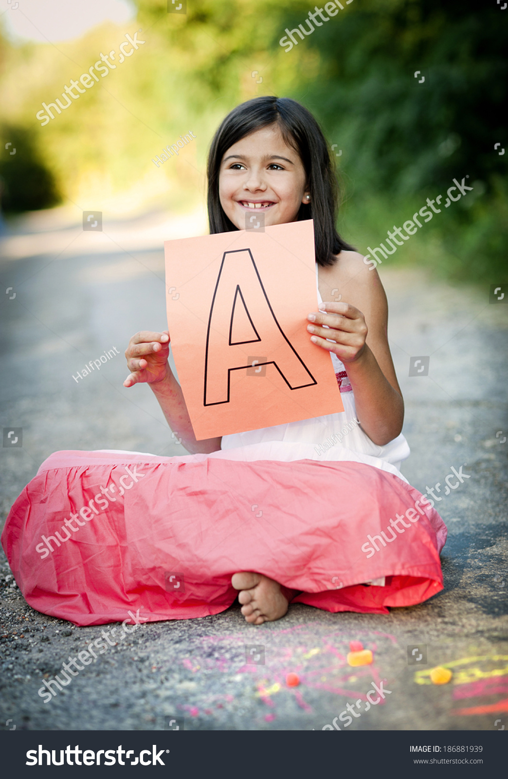 https://image.shutterstock.com/shutterstock/photos/186881939/display_1500/stock-photo-cute-little-girl-is-laughing-and-showing-letter-a-in-green-sunny-park-186881939.jpg