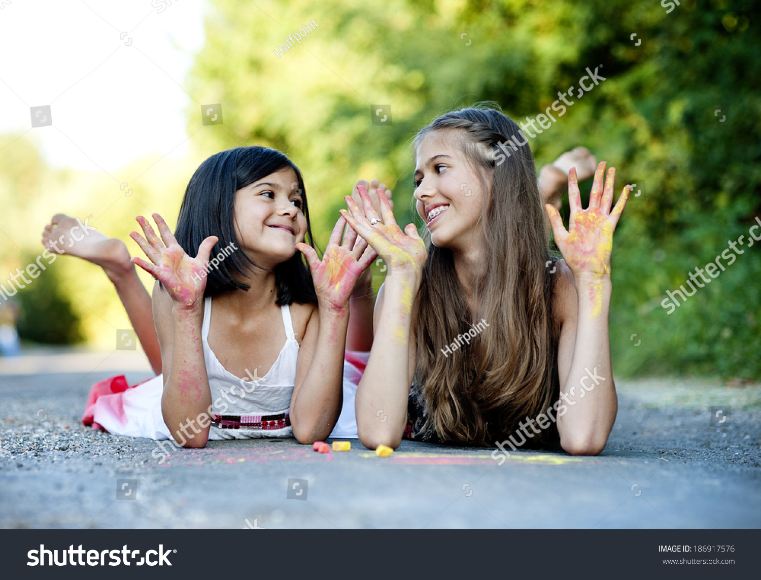 https://image.shutterstock.com/shutterstock/photos/186917576/display_1500/stock-photo-two-sisters-laughing-and-playing-with-chalks-on-pavement-in-green-sunny-park-186917576.jpg