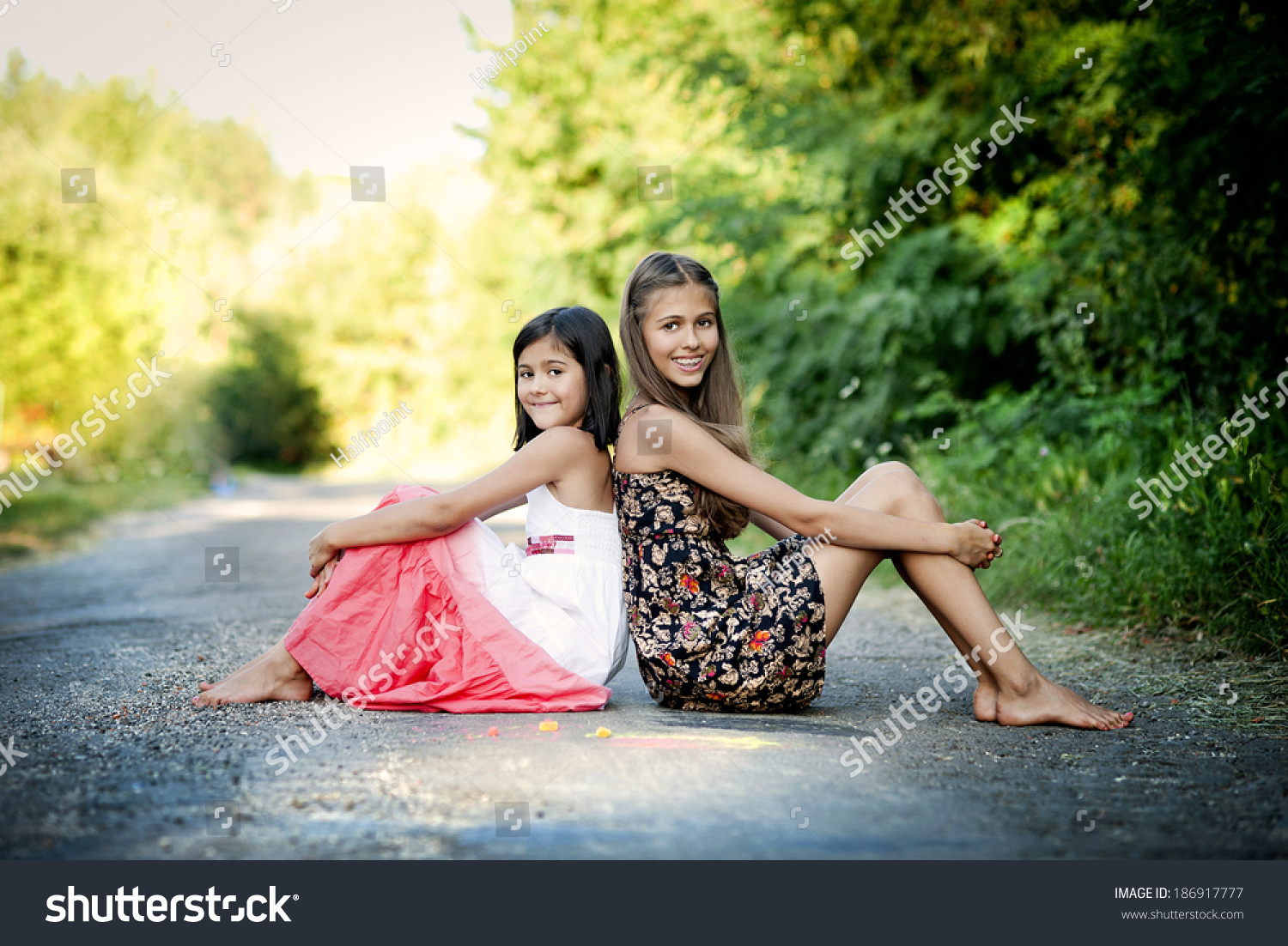 https://image.shutterstock.com/shutterstock/photos/186917777/display_1500/stock-photo-two-sisters-laughing-and-playing-with-chalks-on-pavement-in-green-sunny-park-186917777.jpg