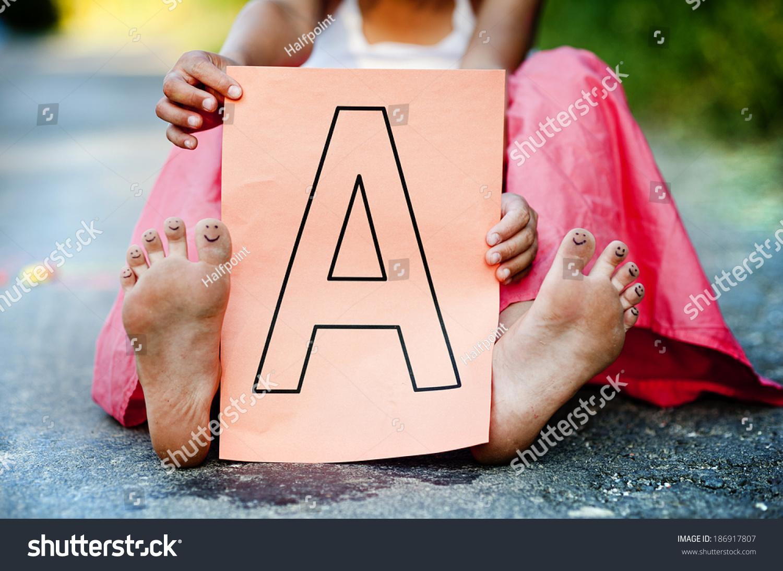 https://image.shutterstock.com/shutterstock/photos/186917807/display_1500/stock-photo-closeup-of-cute-little-girl-showing-letter-a-in-green-sunny-park-186917807.jpg