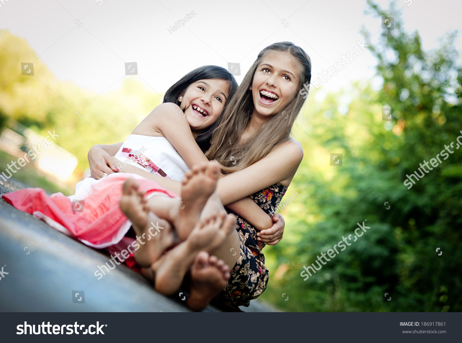 https://image.shutterstock.com/shutterstock/photos/186917861/display_1500/stock-photo-two-sisters-laughing-and-hugging-on-pavement-in-green-sunny-park-186917861.jpg