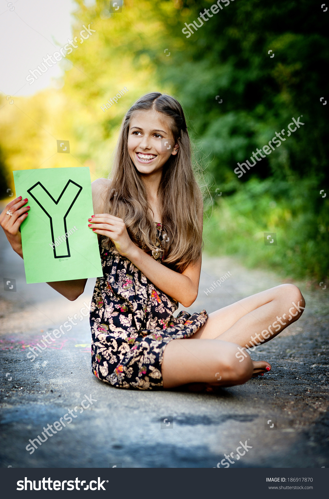 https://image.shutterstock.com/shutterstock/photos/186917870/display_1500/stock-photo-beautiful-teenage-girl-is-smiling-and-showing-letter-y-in-green-sunny-park-186917870.jpg