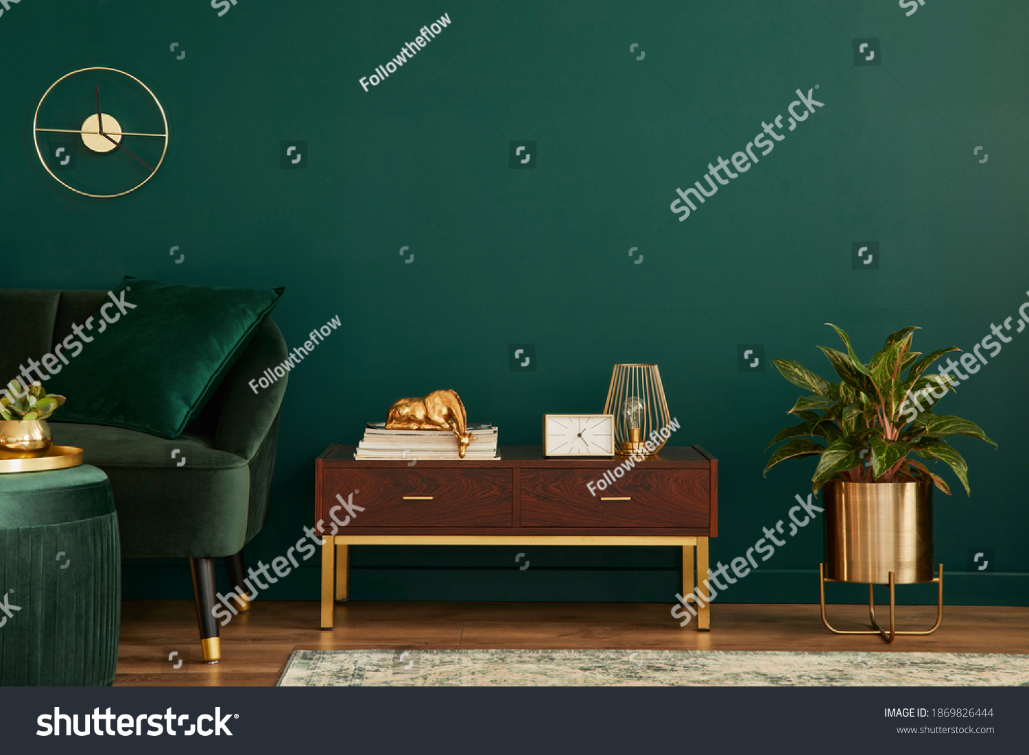 Luxury interior with stylish velvet sofa, wooden commode, pouf, plants, carpet, gold decoration, copy space and elegant personal accessories. Modern living room in classic house. Template. #1869826444