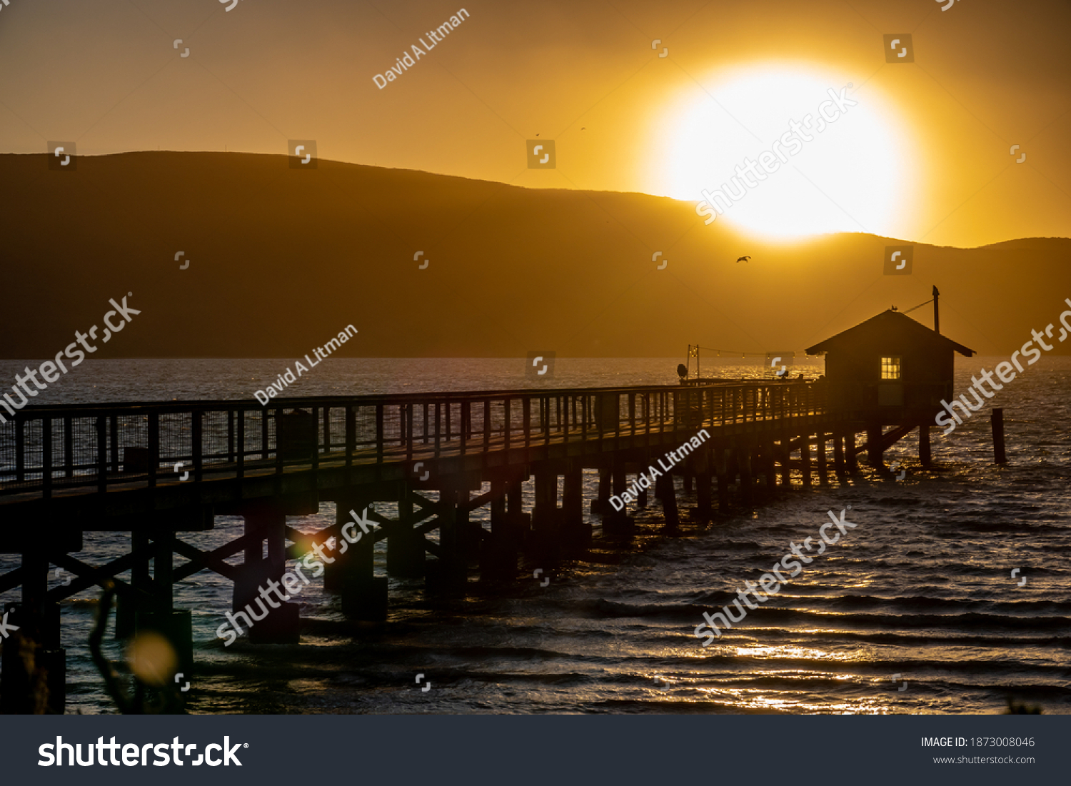 The sun sets over the Point Reyes peninsula as viewed from the shore of Tomales Bay, in Marin County, California, with a pier leading to a boat house in foreground.