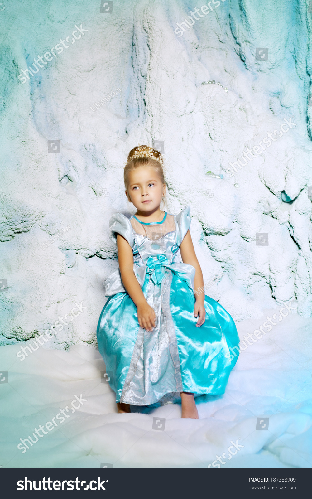 Little girl in princess dress on a background of a winter fairy tale baby snow