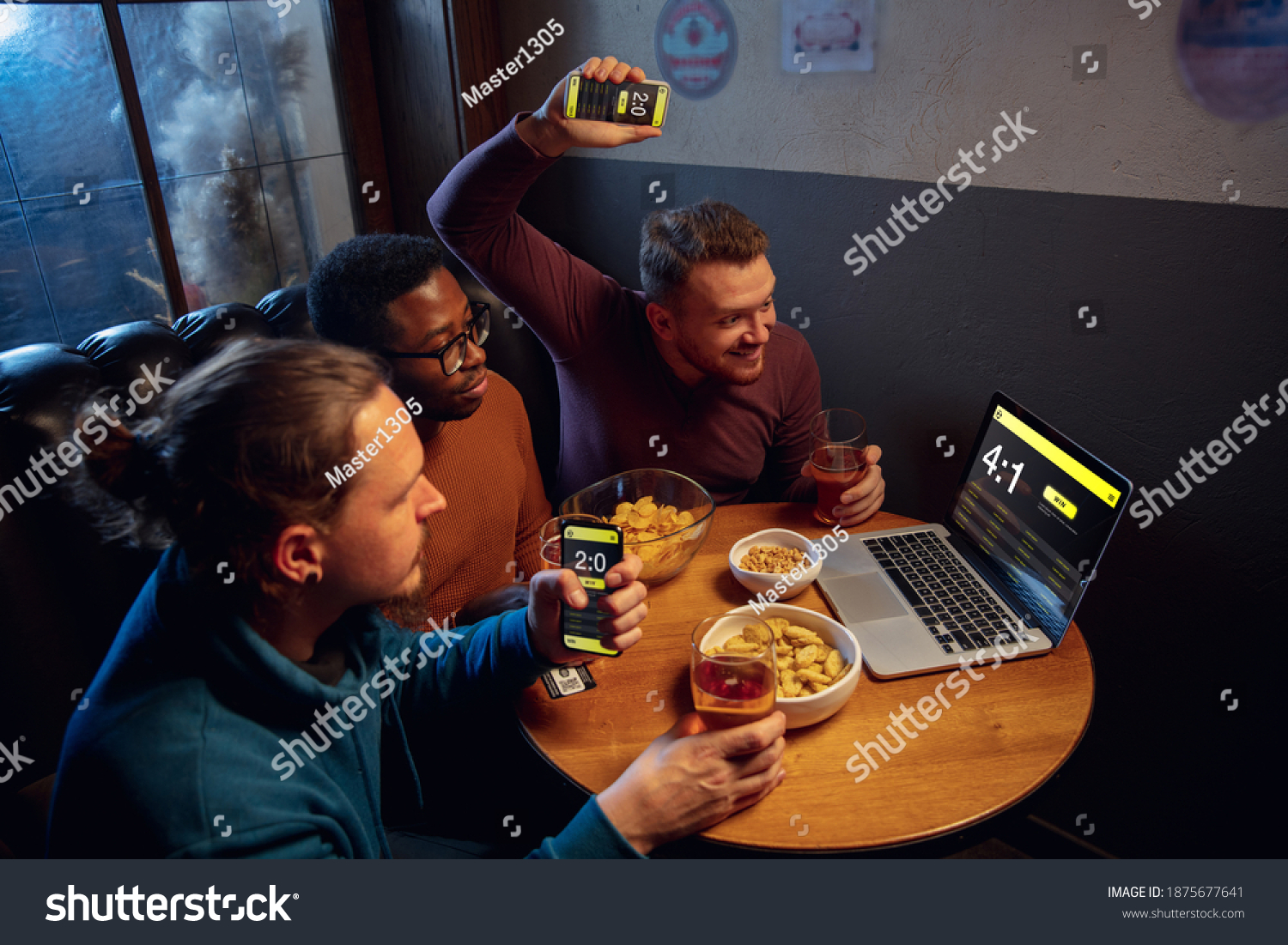 Analyzing. Excited fans in bar with beer and mobile app for betting, score on their devices. Screen with match results, emotional friends cheering. Gambling, sport, finance, modern techn concept. #1875677641