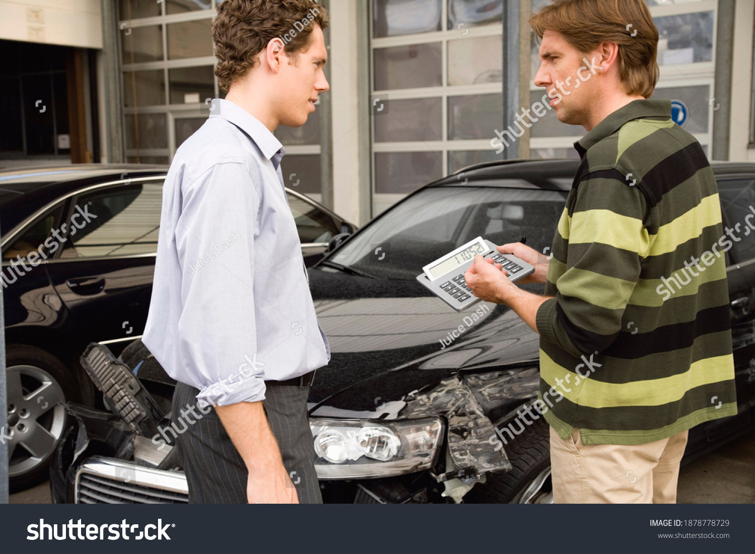 A claims adjuster showing the owner the settlement amount to be paid after assessing the damage done to a car. #1878778729
