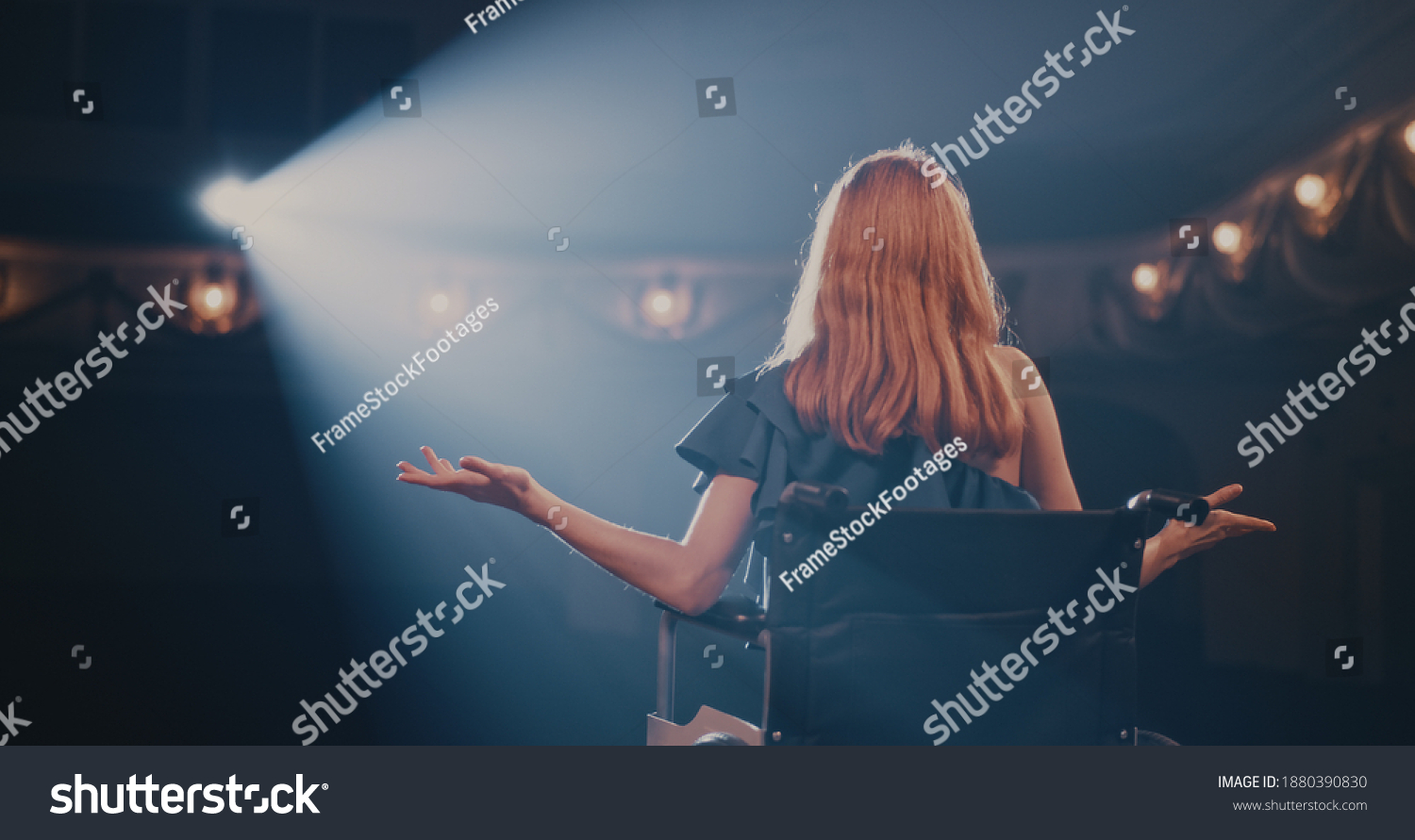 Pan left view of young woman smiling and gesticulating while sitting on wheelchair in spotlight and talking to audience during performance in dark theater #1880390830