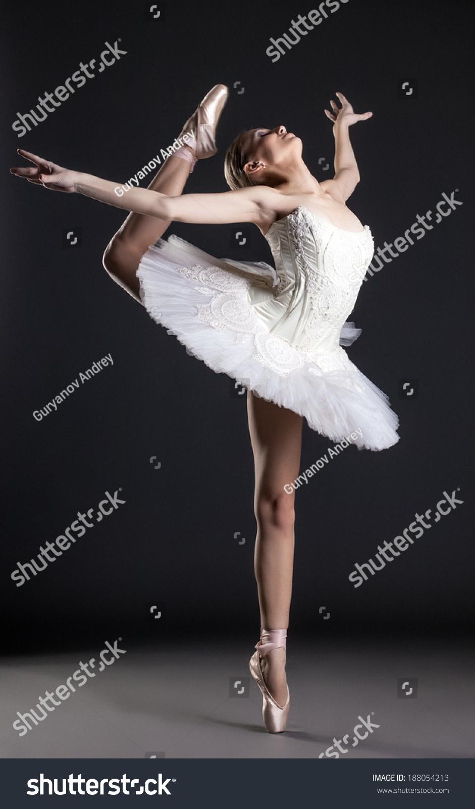 Flexible Dancer Exercising On Pole In Studio Stock Photo