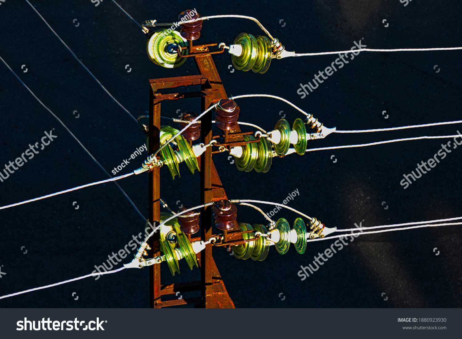 Glass electric insulators mounted on wires of old rusty powertower view from above