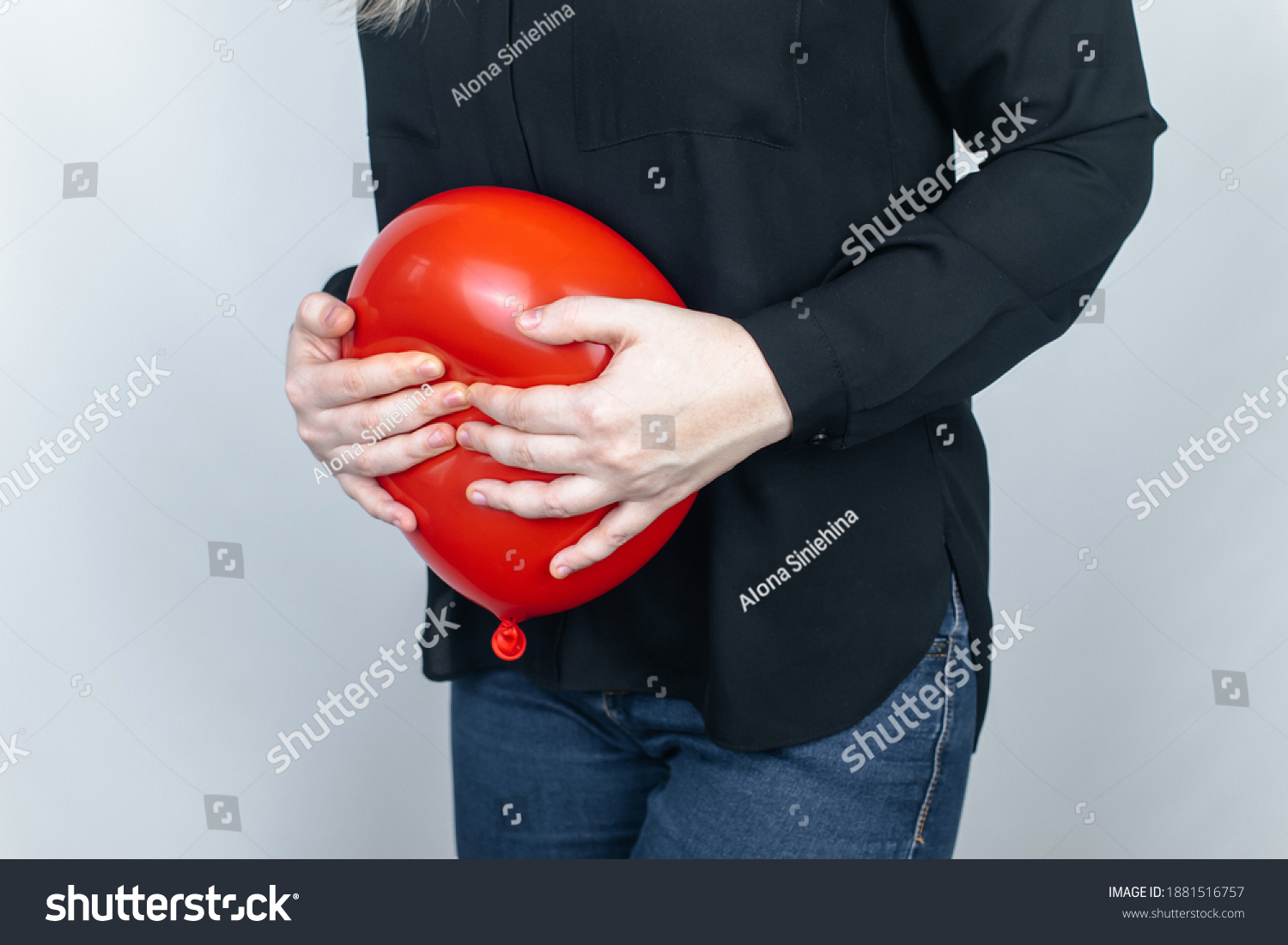 Bloating and flatulence concept. The woman holds a red balloon near the abdomen, which symbolizes bloating. Intestinal tract and digestive system. Problems with flatulence adn gastrointestinal tract #1881516757