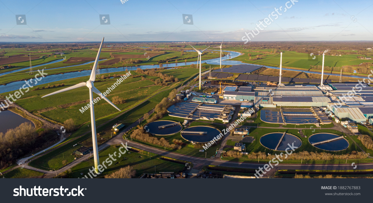 Wind turbines, water treatment and bio energy facility and solar panels in The Netherlands part of sustainable industry in Dutch flat river landscape against blue sky. Aerial circular economy concept. #1882767883