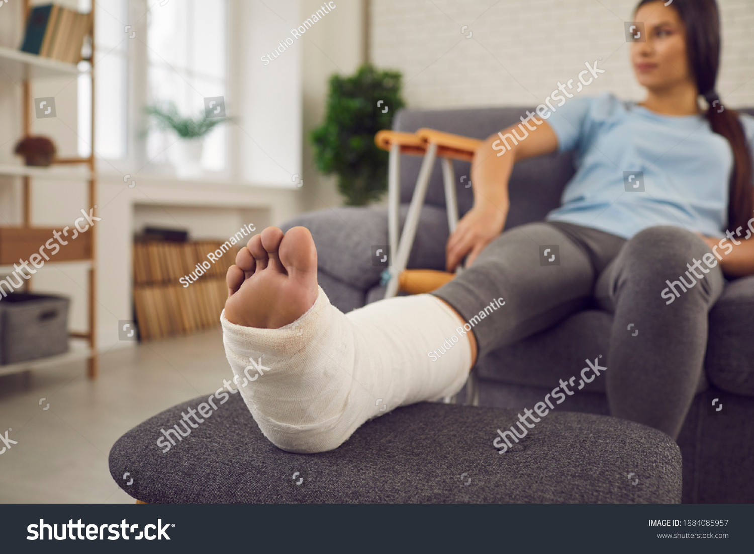 Concept of rehabilitation of people after serious physical accident injury. Female patient with broken leg in plaster cast sitting on sofa. Young woman with foot bone fracture resting on couch at home #1884085957