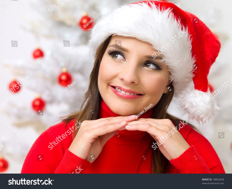 Beautiful woman next to christmas tree wearing red sweater stock photo