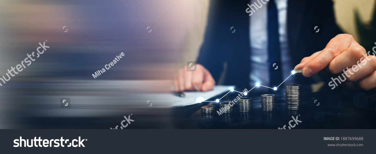 Saving money concept. Hand putting money coin stack with  growing business graph. Panoramic business banner with  copy space. #1887699688