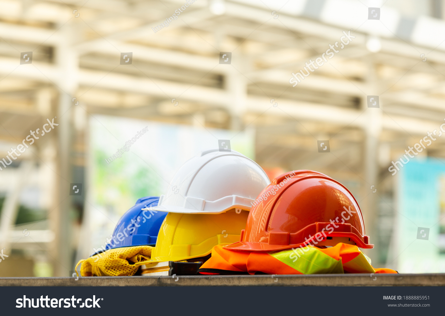 Close up Blue, yellow, white and red hard safety helmet hats for safety project of workman as engineering or project worker place on concrete floor city outdoor. #1888885951