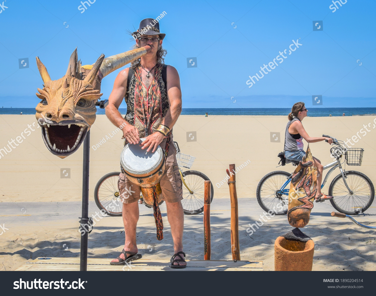 Venice Beach, California - July 11, 2015: A musician plays a dragon headed didgeridoo as a woman rides her bicycle at the Venice Beach Boardwalk.