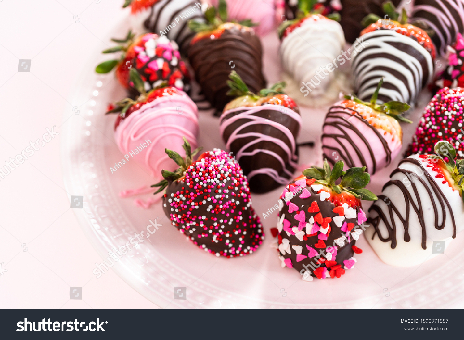 Variety of chocolate dipped strawberries on a pink cake stand. #1890971587